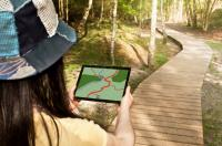 Woman following a map on a tablet while on a hike